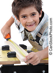 Young boy measuring a piece of wood to cut