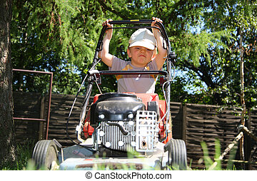 Young boy mowing grass