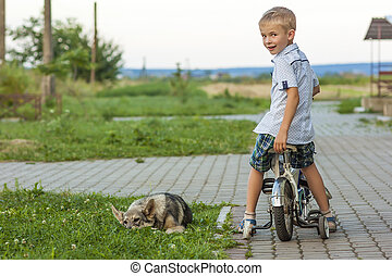 Young boy on a bicycle and sleeping dog