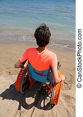 young boy on a wheelchair by the sea