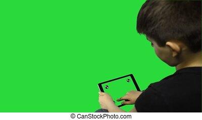 Young boy on chroma key using smart device