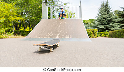 Young Boy on Ramp Looking at Skateboard at Bottom