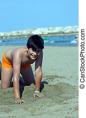 Young boy on the beach playing with sand