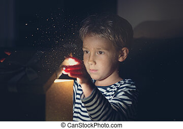 Young boy opening a golden gift box with sparkling light