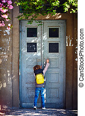 young boy opening the rusty old house door