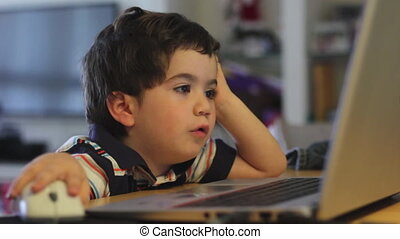 young boy operating educational game on a laptop - Shot of...
