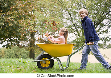 Young boy outdoors pushing young girl in wheelbarrow and...