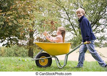 Young boy outdoors pushing young girl in wheelbarrow and...