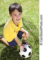 Young Boy Outside Playing With Football or Soccer Ball
