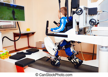 young boy passes robotic gait therapy in rehabilitation...