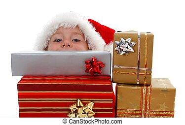Young boy peeking above gifts