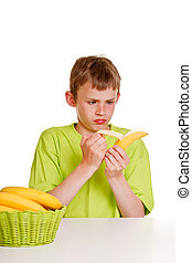 Young boy peeling a banana with distaste - Young boy peeling...