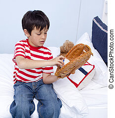 Young boy playing baseball in his bedroom