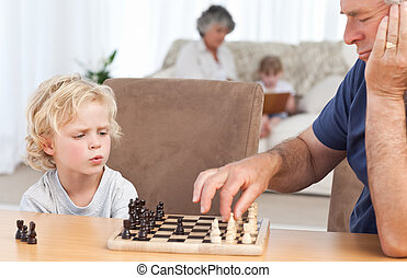 Young boy playing chess with his grandfather