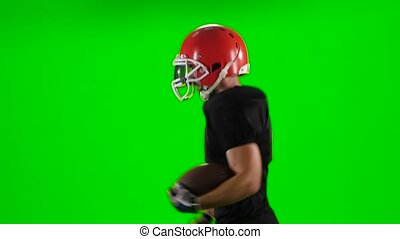 Young boy playing football in a red helmet. Green screen