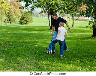 Young boy playing football with his father