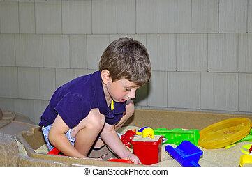 Sandbox - Young Boy Playing in a Sandbox