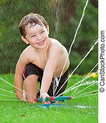 Young boy playing in water sprinkler
