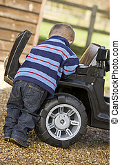 Young boy playing outdoors with toy truck