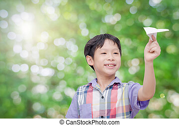 Young boy playing paper airplane