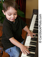 young boy playing piano - a male youth practicing songs on...
