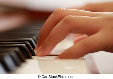 Young boy's hand playing upright piano. Close up view from left side.