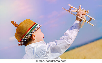 Young boy playing with a model airplane