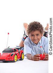 Young boy playing with a red remote control sports car