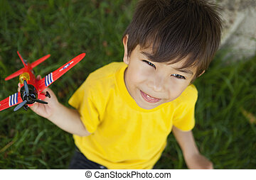 Young boy playing with a toy plane at park - High angle view...