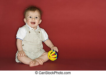 Young boy playing with ball.