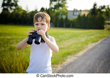 Young boy playing with binoculars on a sunny day.