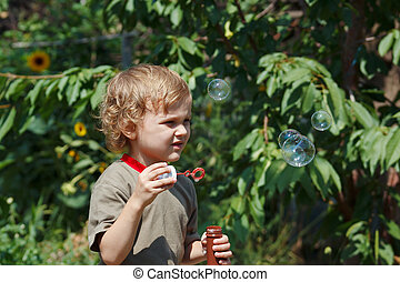 Young boy playing with bubbles outdoors on a sunny day