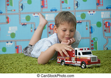 young boy playing with car on the carpet