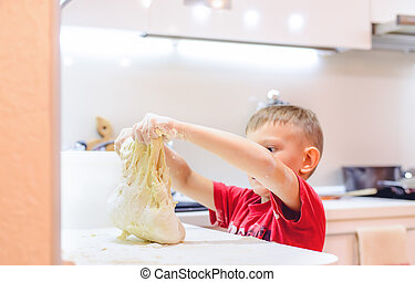 Young boy playing with dough while baking