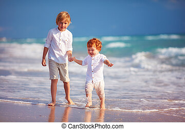young boy playing with junior brother on sandy beach