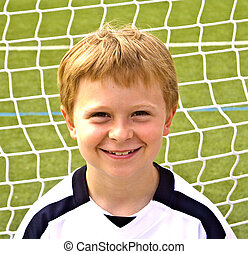 young boy plays soccer and enjoys it
