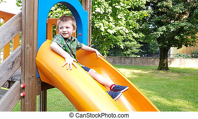 young boy plays with a slide in the park