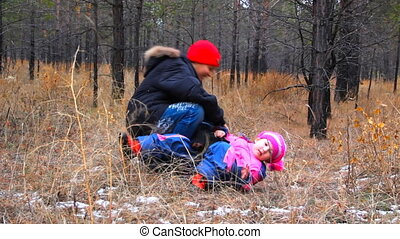 Young boy plays with sister in the autumn forest.