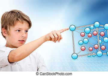 Young boy pointing at 3D molecules.