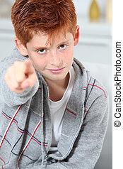 Young boy pointing at camera