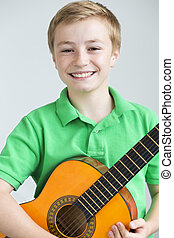 Young boy posing with a guitar