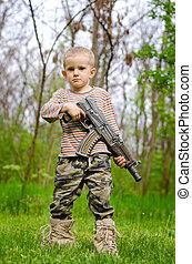 Young boy posing with machine gun