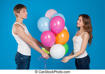 Young boy presenting balloons to a girl