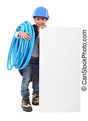 Young boy pretending to be a plumber with a board left blank for your message