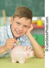 boy putting a coin in a piggy bank