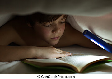 Young boy reading a book under the blanket or quilt