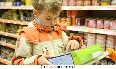 young boy reading inscription on goods box in supermarket