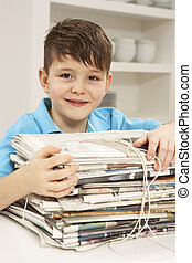 Young Boy Recyling Newspapers At Home