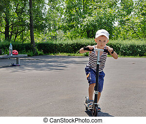 Young boy riding a scooter in a park