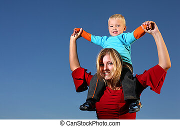 Young boy riding on his mother's shoulders, outdoors , blue sky behind.
